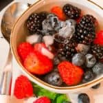 Nature's Cereal Recipe- Raspberries, Blueberries & Blackberries In A Bowl Of Coconut Water With Ice & A Spoon