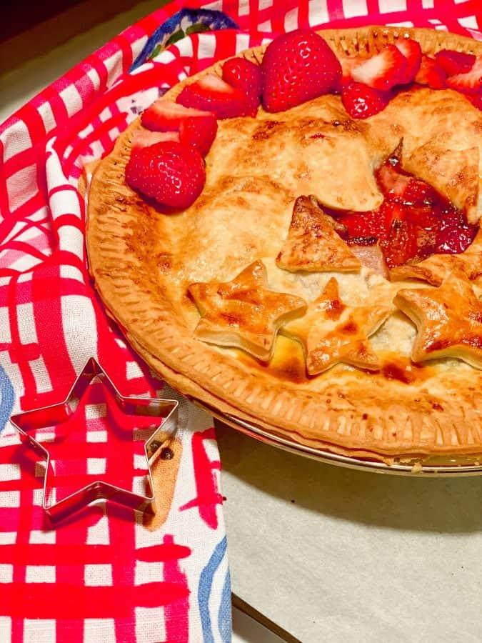 Easy Strawberry Rhubarb Pie Recipe - pie pictured with decorative stars, cookie cutter and red white and blue dish towel